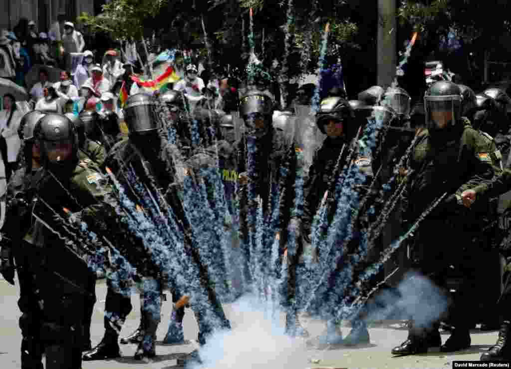 A firecracker explodes next to riot police during a protest rally against new health-care policies in La Paz, Bolivia. (Reuters/David Mercado)