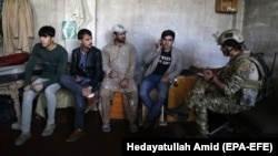 An Afghan soldier speaks with staff from Shamshad TV who were rescued after armed men attacked the TV station in Kabul on November 7. Two security guards were killed in the attack.