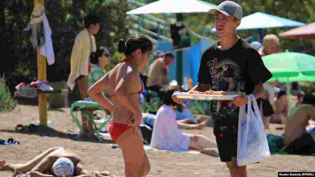 Юноша предлагает отдыхающим на озере купить беляши.