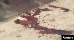 Blood stains are seen on the ground at the cafe after the shooting.