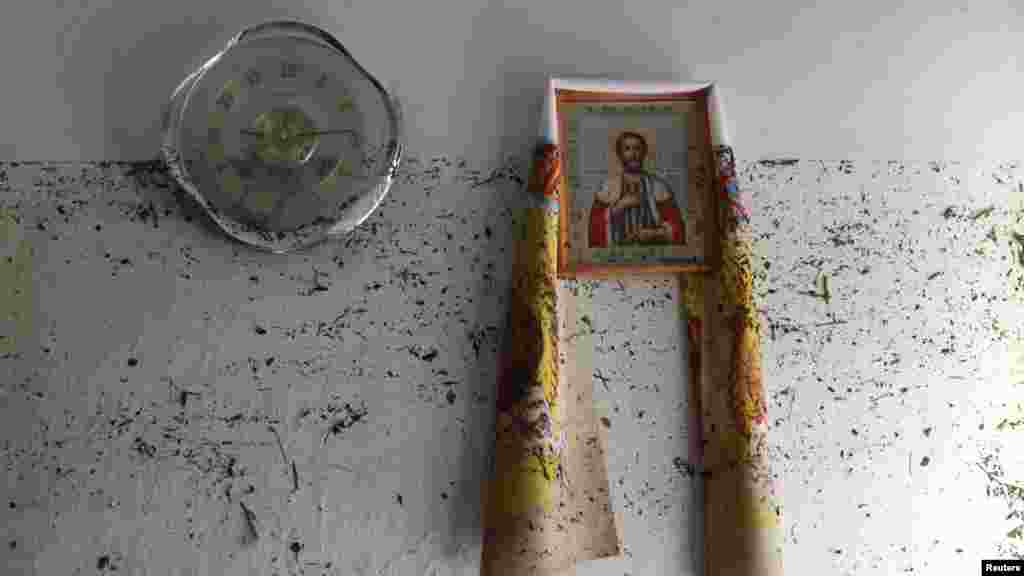 An icon hangs on the wall with dirt from the floodwaters marking it, in the town of Krymsk in the Krasnodar region.