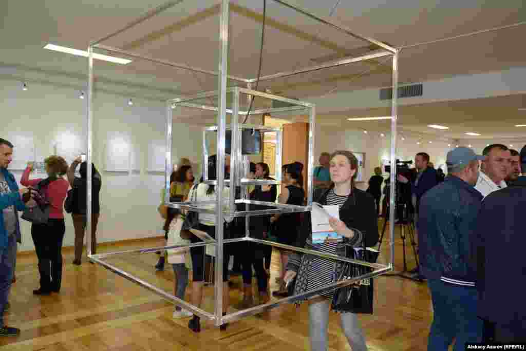 «Куб» – совместная инсталляция Вагифа и Наргис Рахмановых. Это кубической формы металлический каркас, подвешенный к потолку. Внутри – куб поменьше. В нем – еще более маленький куб. Внутри последнего – плеер, из которого раздается музыка французского композитора Яниса Ксанакиса, создателя стохастической музыки (разновидность электронной музыки). Если у Ксанакиса музыка взаимодействует с математикой, то в инсталляции Рахмановых музыка взаимодействует с геометрией.