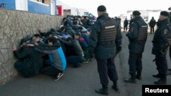 Russian police detain migrant workers during a raid on the Pokrovsky vegetable storage depot in the Biryulyovo district of Moscow on October 14, one day after the rioting sparked by the killing.