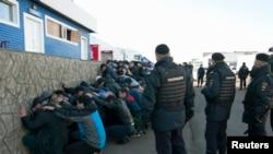 Россия - Полиция задерживает рабочих-мигрантов во время набега в овощном складском комплексе в районе Бирюлиово Москвы 14 октября 2013