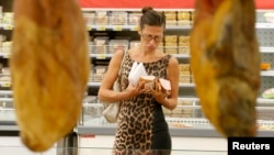 A customer tries to decide which meat to choose at a grocery store in Moscow on August 18.
