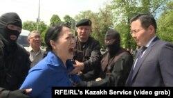 Полицейские задерживают Гайни Еримбетову, мать арестованного бизнесмена Искандера Еримбетова (которого ряд казахстанских правозащитников назвали политзаключенным), пришедшую на несанкционированную акцию с требованиями «освободить политических заключенных» и «прекратить пытки». Алматы, 10 мая 2018 года.