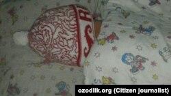 Воспитанник детского сада №1 в Хаджаабадском районе Андижанской области спит в обеденное время в теплой шапке.