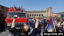 ARMENIA -- Supporters of opposition lawmaker Nikol Pashinian react standing on top of a vehicle as they protest in Republic Square in Yerevan on Wednesday, May 2, 2018.