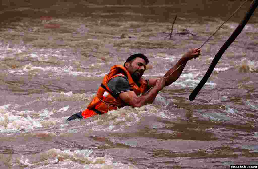 A State Disaster Response Force member searches for a man who drowned during flash floods in Tailbal on the outskirts of Srinagar, India. (Reuters/Danish Ismail)