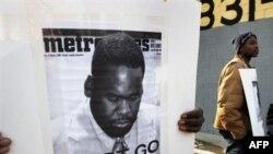 Кваме Килпатрик (на плакате) упорно сопротивляется требованиям общественности оставить свой пост