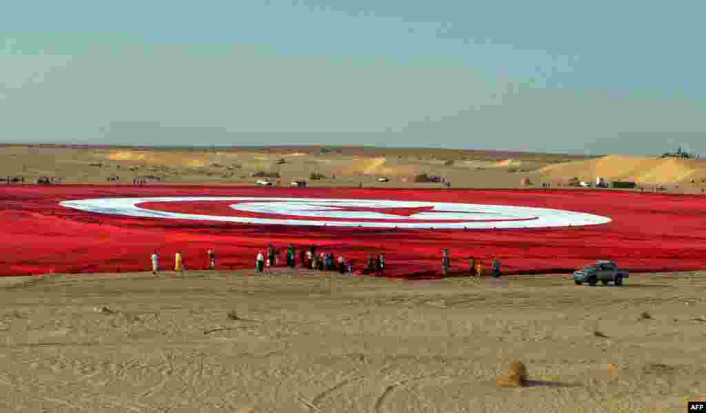 A giant Tunisian national flag is unfurled at Ong Jmel in the southern desert. The flag is the size of 19 football pitches and is a bid to set a Guinness world record and promote patriotism in the face of Islamist extremism. (AFP/Saif Trabelsi)