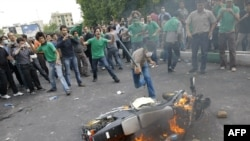 Supporters of Iranian presidential candidate Mir Hossein Musavi burn a police motorcycle during a protest on Valiasr Street in Tehran on June 13, 2009.