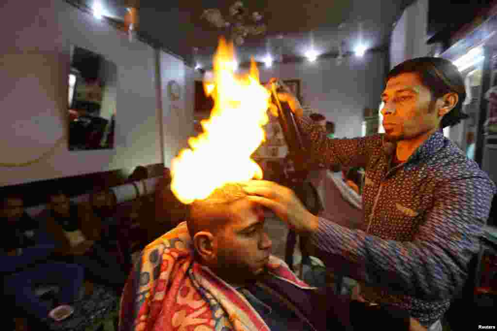 Palestinian barber Ramadan Odwan styles and straightens the hair of a customer using fire at his salon in Rafah in the southern Gaza Strip. (Reuters/Ibraheem Abu Mustafa)