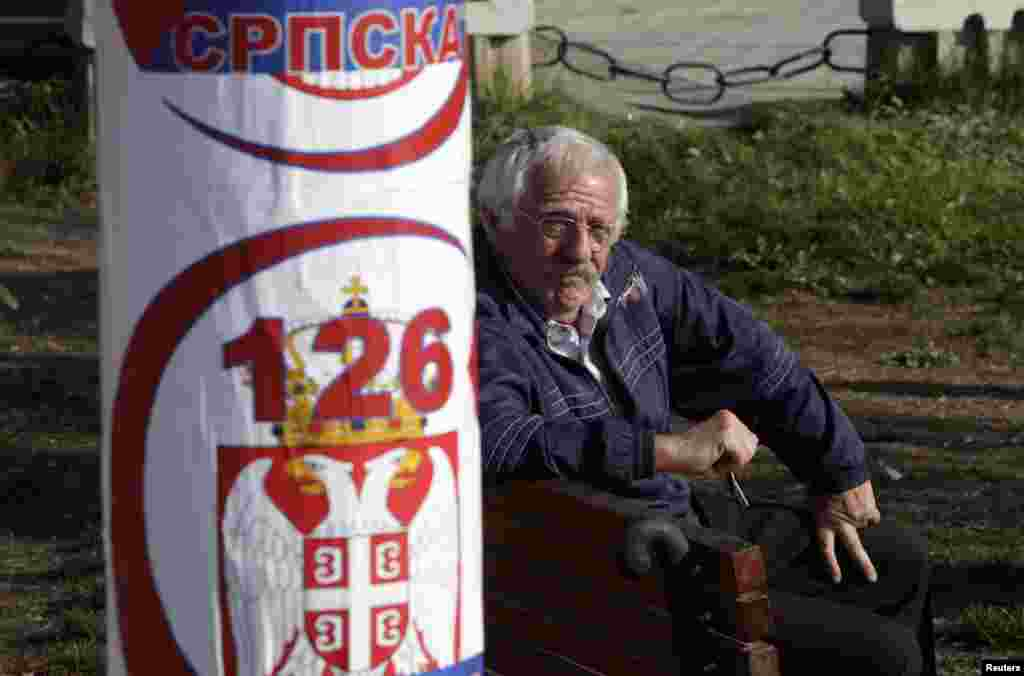 A Kosovar Serb sits near a poster for the Serbian Citizens' Initiative political party in the town of Gracanica, which is inhabited by a Serbian minority.