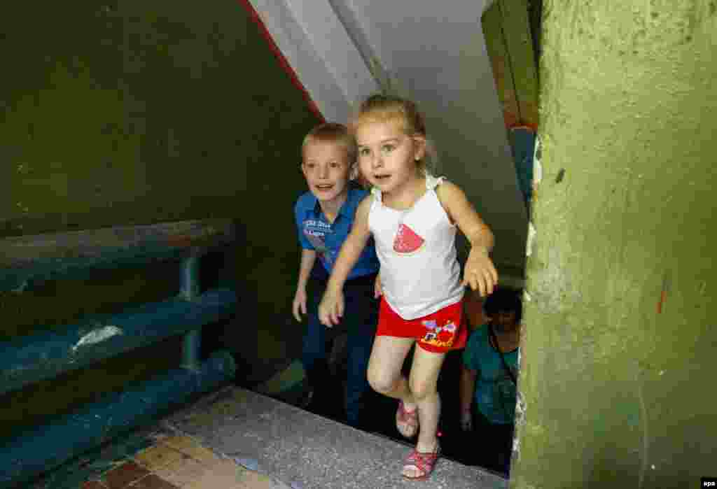 Local children Ulyana and Sergei leave a bomb shelter which they are using as living quarters after their homes were destroyed in shelling not far from the front line in Donetsk, eastern Ukraine. (epa/Alexander Ermochenko)