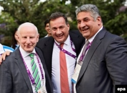 The president of the European Olympic Committee, Patrick Hickey (left), and Sports Minister Azad Rahimov pose with an unidentified man on June 11 in Baku.