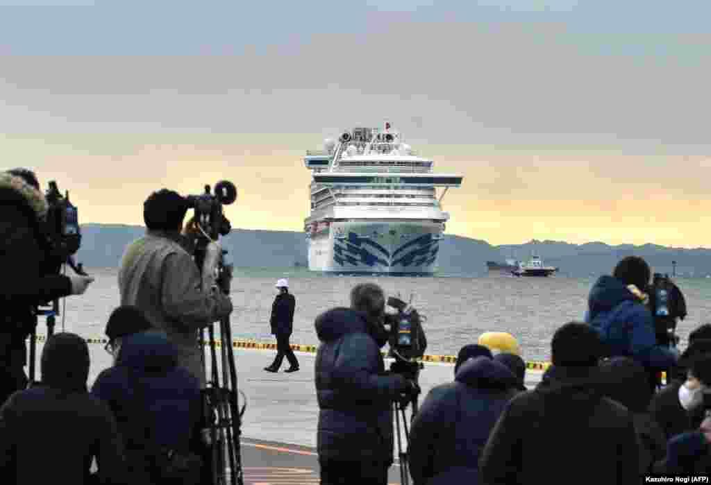 Vasul de croazieră este ancorat în rada portului Yokohama, iar ambarcațiuni ale poliției japoneze patrulează pentru a împiedica civili să se apropie.