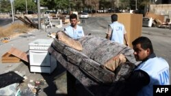 БУУнун кызматкерлери үйүнөн куулган Нассар ал-Гавинин үй-бүлөсүнө үйүндөгү жүктөрдү чыгарып беришүүдө, 3-август, 2009.