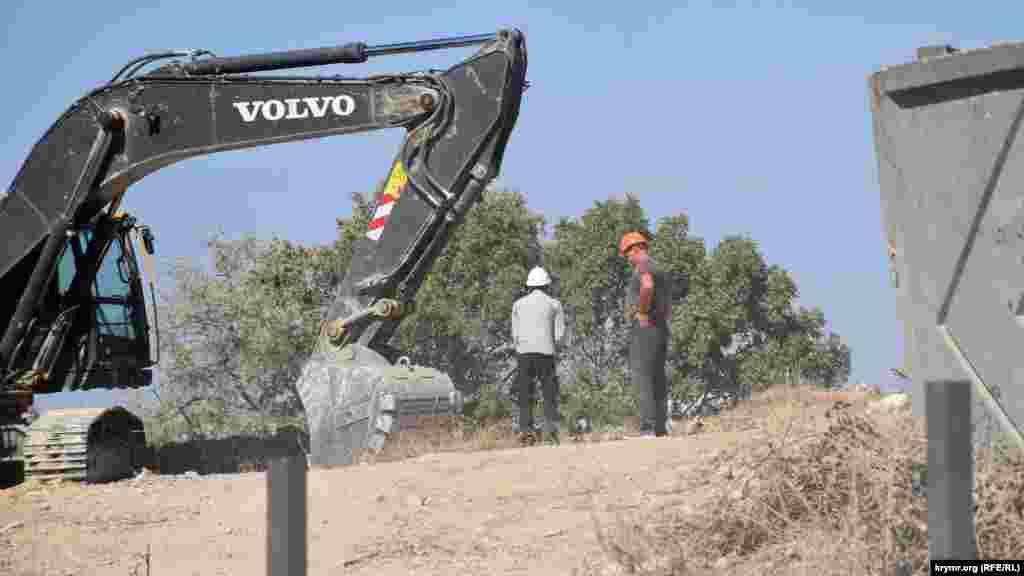 Экскаватор роет яму на территории строительства