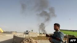 Афганский полицейский стоит недалеко от места взрыва бомбы. Иллюстративное фото.