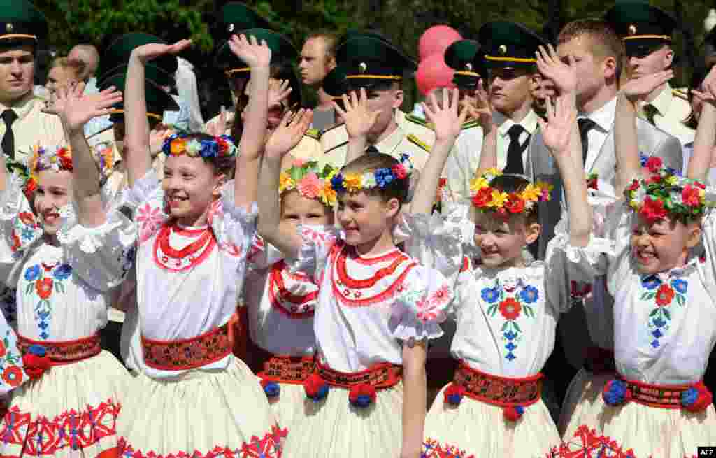 Belarusian girls, wearing traditional costumes, take part in Victory Day celebrations in Minsk. (AFP/Viktor Drachev)