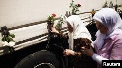 На машини з трунами в Сараєві чіпляють квіти, 9 липня 2012 року