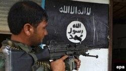 سرباز افغان در مقابل دفتر تسخیر شده گروه داعش در ولسوالی اچین ولایت ننگرهار. 26 July 2016