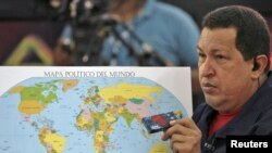 "Venezuela -- President Hugo Chavez holds a chocolate bar and a map during his weekly ""Alo Presidente"" broadcast in the town of Caucagua, 31Oct2010"