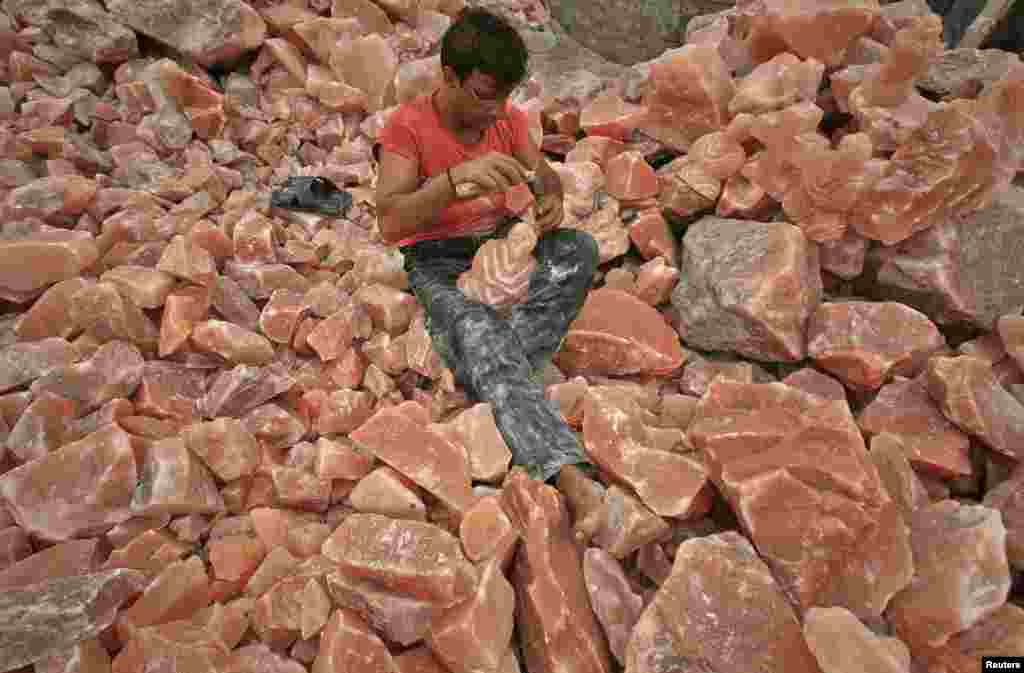 A man in Lahore applies the final touches to a sculpture made from rock salt.