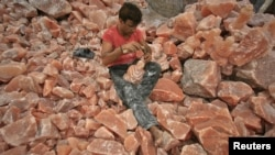 A man applies the final touches to a sculpture made from Himalayan pink rock salt on the outskirts of Lahore.