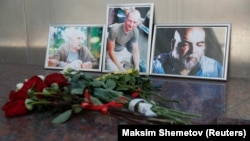 Photographs of journalists Orkhan Dzhemal (right), Kirill Radchenko (center) and Aleksandr Rastorguyev are seen at a small memorial to the slain jounalists outside the Central House of Journalists in Moscow.