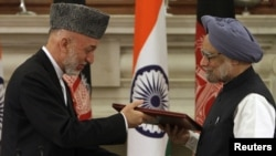 Indian Prime Minister Manmohan Singh (right) greets Afghan President Hamid Karzai in New Delhi
