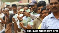 Voters show their National Identity Cards as they line up to cast their ballot during general elections in Karachi on July 25