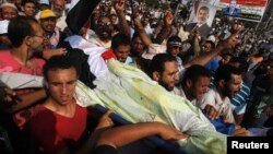 Прихильники Мухаммада Мурсі несуть тіло вбитого товариша під час стрілянини біля штаб-квартири Республіканської гвардії в Каїрі, 8 липня 2013 року