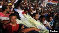 Сторонники Мухаммеда Мурси несут тело погибшего в столкновениях у здания Республиканской гвардии