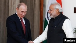 Russian President Vladimir Putin (left) shakes hands with Indian Prime Minister Narendra Modi during a photo opportunity ahead of their meeting at Hyderabad House in New Delhi on December 11.