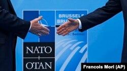 АҚШ президенти Трамп (чапда) НАТО бош котиби Йенс Столтенберг билан саммит олдидан сўрашмоқда. Брюссель, 2018, 11 июль.