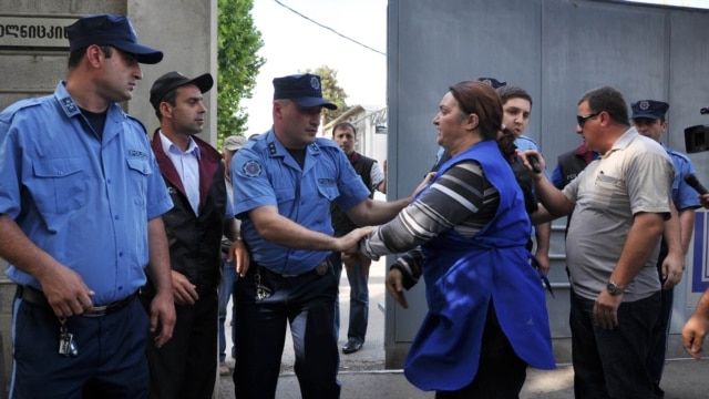 Georgian police grapple with workers as they seize dishes at a satellite TV outlet on June 1.