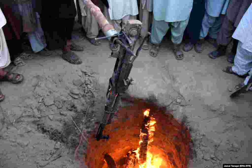 A Kalashnikov is thrown in a fire as a symbol to end enmity among different tribes in Balochistan Province during a jirga meeting in Qila Abdullah, Pakistan. (EPA-EFE/Jamal Taraqai)