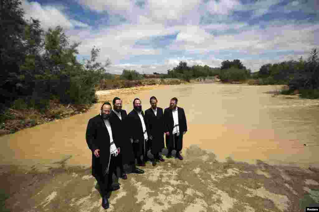 Ultra-Orthodox Jewish men pose for a friend to take their photograph near the flooded Besor stream in Israel's southern Negev desert near Kibbutz Zeelim on May 8. This week, Israel was hit by unseasonal heavy rain. (Reuters/Amir Cohen)