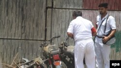 Security officials inspect the scene of a bombing in Karachi on June 10 that killed one person.