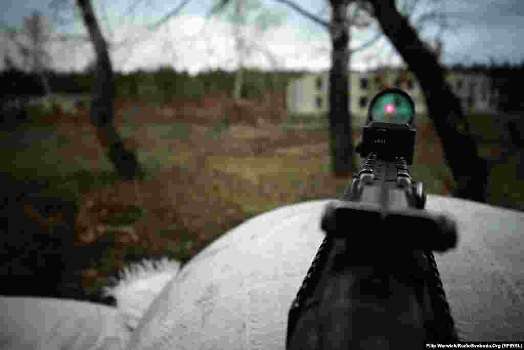 Військовий демонструє оптику автоматичної зброї