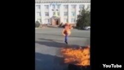 """Ерлан Бектібаевтың """"Нұр Отан"""" партиясы ғимараты алдында өзін-өзі өртеген видеосынан скриншот. Тараз, 24 қазан 2015 жыл."""