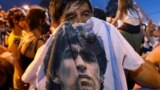 People mourn soccer legend Diego Maradona outside the morgue