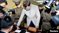 Солтүстік Корея сотына кірер кезде саусағын сканерден өткізіп жатқан АҚШ студенті Отто Уормбир