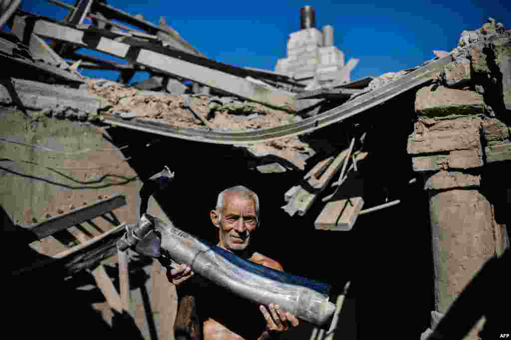 A Ukrainian man holds a piece of a rocket in his destroyed house after shelling in the village of Olenivka, south of the besieged rebel stronghold of Donetsk, on August 20. (AFP/Dimitar Dilkoff)