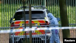 A police forensics investigator approaches a crime scene where one man was killed in Woolwich in southeast London.