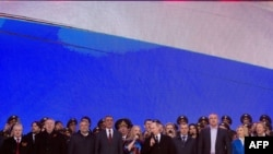 Russian President Vladimir Putin (center) and other officials sing the national anthem as they take part in a rally and concert by the Kremlin Wall in central Moscow on March 18.