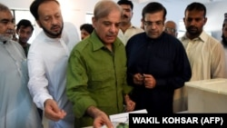 Shahbaz Sharif (center), the younger brother of ousted Pakistani Prime Minister Nawaz Sharif, casts his vote in the general elections.