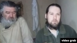 The two Moldovan pilots are seen in an undated video released by the Taliban.